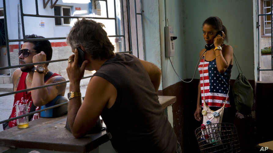 A woman talks on the phone at a coffee shop, in Havana, Cuba, March 15, 2016. Five days ahead of the first presidential trip to Havana in nearly 90 years, the U.S. eliminated a ban on Cuban access to the international banking system.