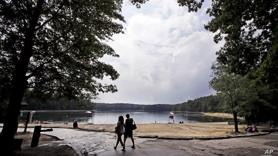 A couple walks along the shore of Walden Pond in Concord, Mass., July 12, 2017.