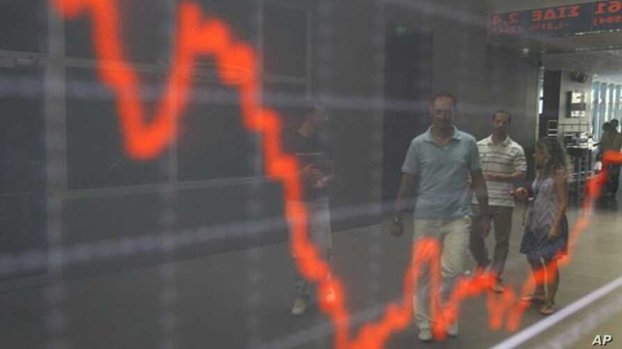 People are reflected at an index board inside the Athens stock exchange August 9, 2011.