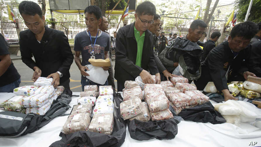 FILE - Thai policemen display intercepted drugs - 226 kilograms (498 pounds) of crystal meth and 8 kilograms (18 pounds) of heroin - during press a conference in Bangkok, Thailand, March 24, 2016. Thai police arrested 15 Malaysians as part of the hei