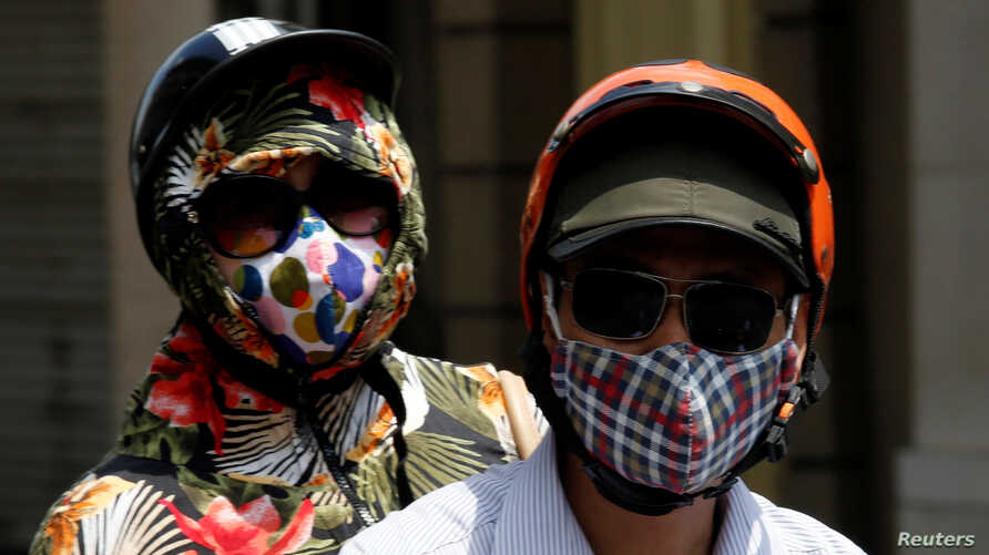 People wear protective masks while riding on a street in Hanoi, Vietnam, May 21, 2018.