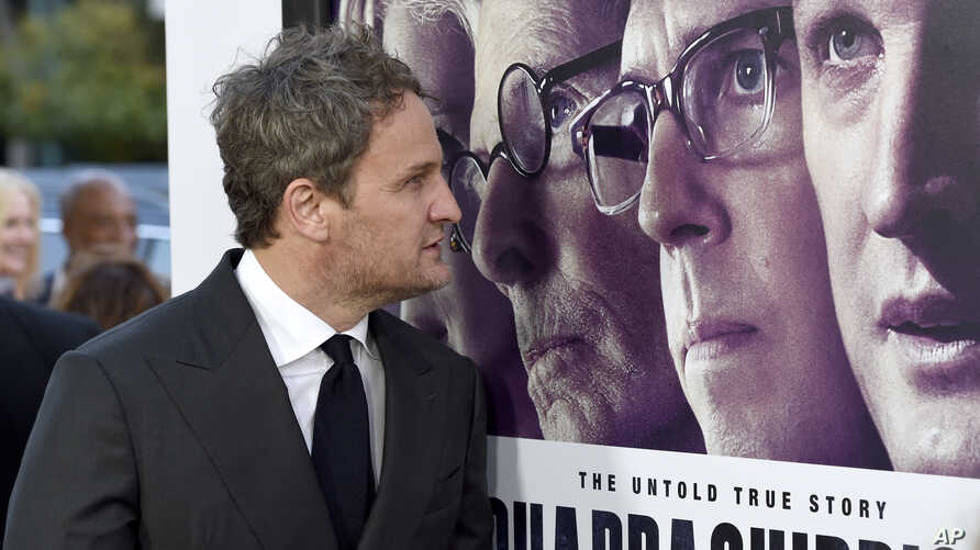 """FILE - Jason Clarke looks at a movie poster as he arrives at the premiere of """"Chappaquiddick"""" at the Samuel Goldwyn Theater, March 28, 2018, in Beverly Hills, Calif."""