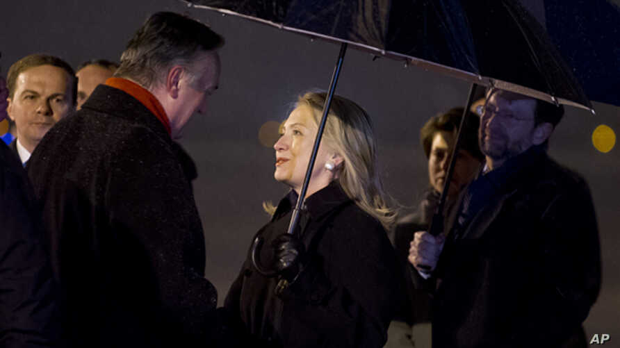 Foreign Minister of Bosnia Herzegovina, Zlatko Lagumdzija  (l) greets US Secretary of State Hillary Clinton upon her arrival at the Sarajevo Airport, Oct. 29, 2012.
