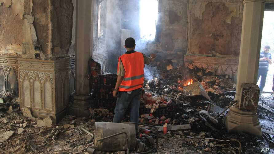 An Egyptian takes video of the burning remains of the Rabaah al-Adawiya mosque, in the center of the largest protest camp of Morsi supporters that was cleared by security forces, Nasr city, Cairo, August 15, 2013.