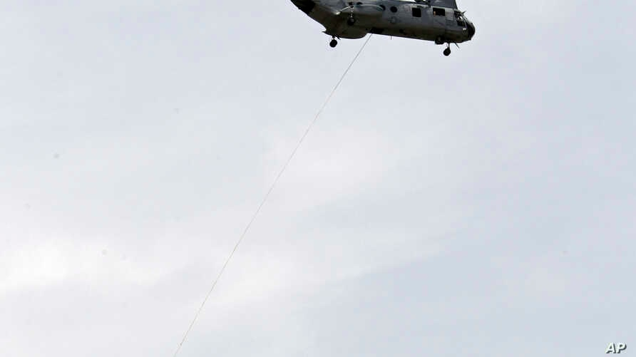 """FILE - A CH-46 """"Sea Knight"""" helicopter snatches four Marines off the runway at Burke Lakefront Airport in Cleveland."""