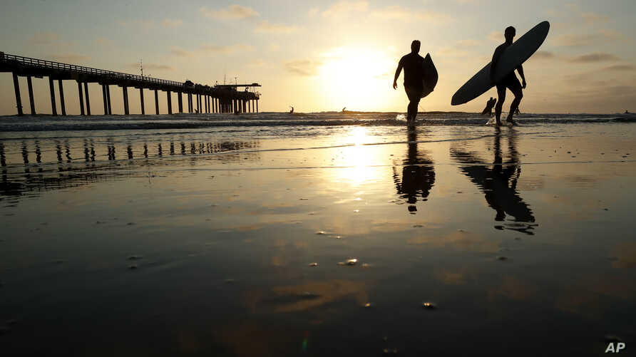 Surfers leave the water next to Scripps Pier, Aug. 2, 2018, in San Diego. A recent measurement of seawater temperature off Scripps Pier broke a record — it reached 79.5 degrees Fahrenheit on Aug. 9.
