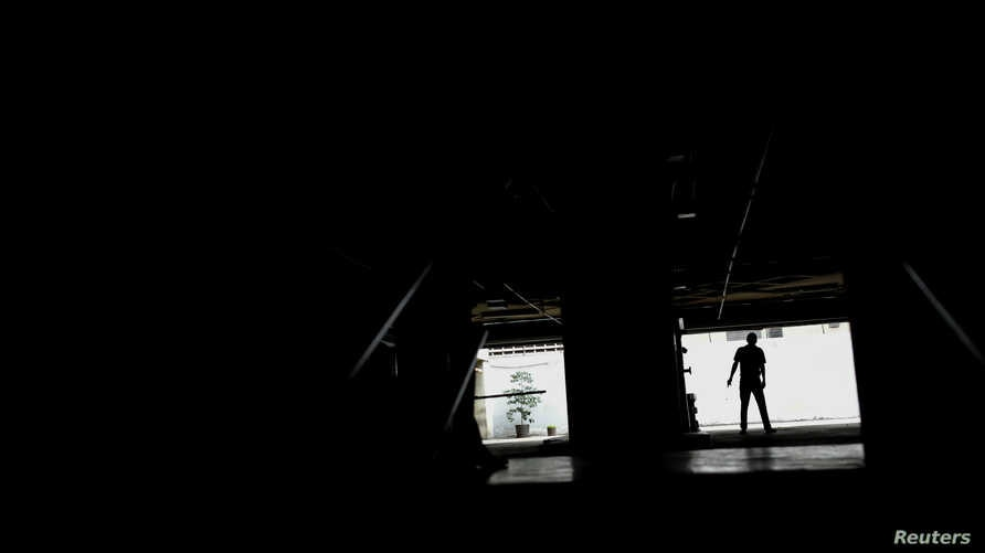 A man walks at a parking garage during a blackout in Caracas, Venezuela, Feb. 6, 2018.