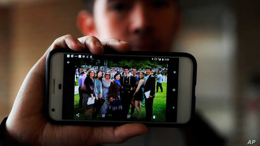 In this April 10, 2018, photo, Amos Cao, son of Chinese Rev. John Sanqiang Cao, holds a family photo showing his father, far right, in Ann Arbor, Mich.