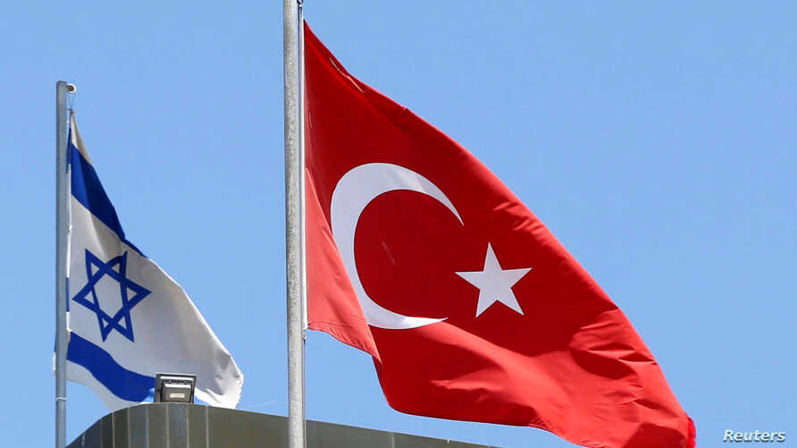 A Turkish flag flutters atop the Turkish embassy as an Israeli flag is seen nearby, in Tel Aviv, Israel, June 26, 2016.