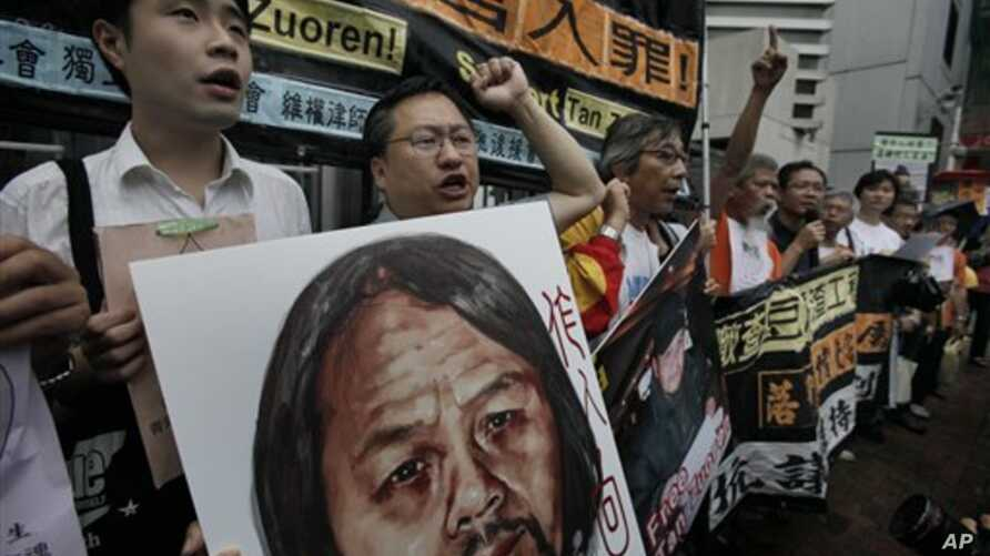 Protesters raise picture of Chinese dissident Tan Zuoren during outside Chinese government's liaison office, Hong Kong, June 9, 2010.