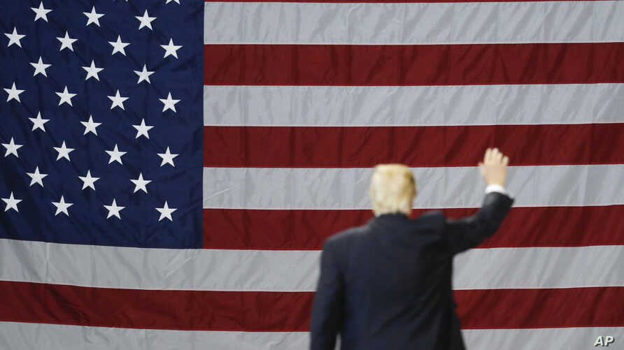 FILE - President Donald Trump waves in front of an American flag as he leaves after speaking during a rally at the Kentucky Exposition Center, March 20, 2017, in Louisville, Kentucky.