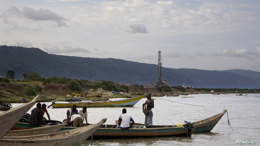 FILE - Fishermen row their boats next to an oil exploration site in Bulisa district, approximately 244 kilometers northwest of Kampala in this undated handout photo from Tullow Oil Uganda, July 2012.