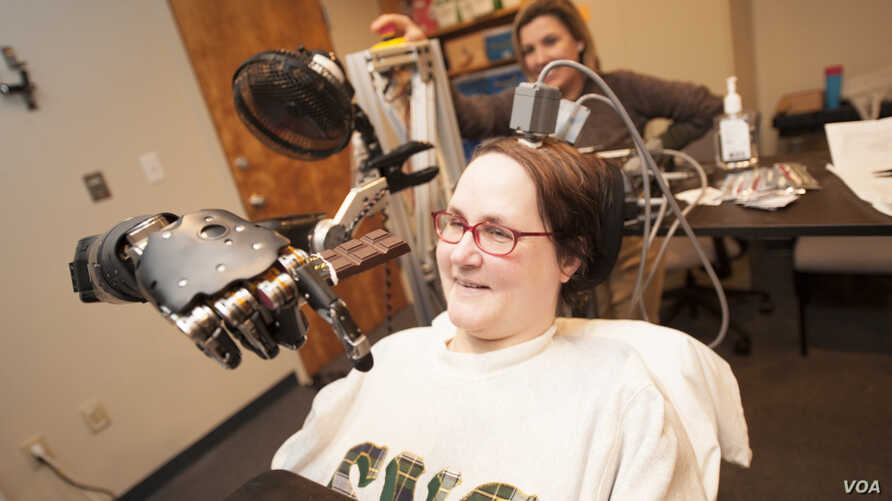 Jan Scheuermann, who has quadriplegia, brings a chocolate bar to her mouth using a robot arm she is guiding with her thoughts. Researcher Elke Brown, M.D., watches in the background. Click the photo to download it in high resolution,  Photo credit: ""