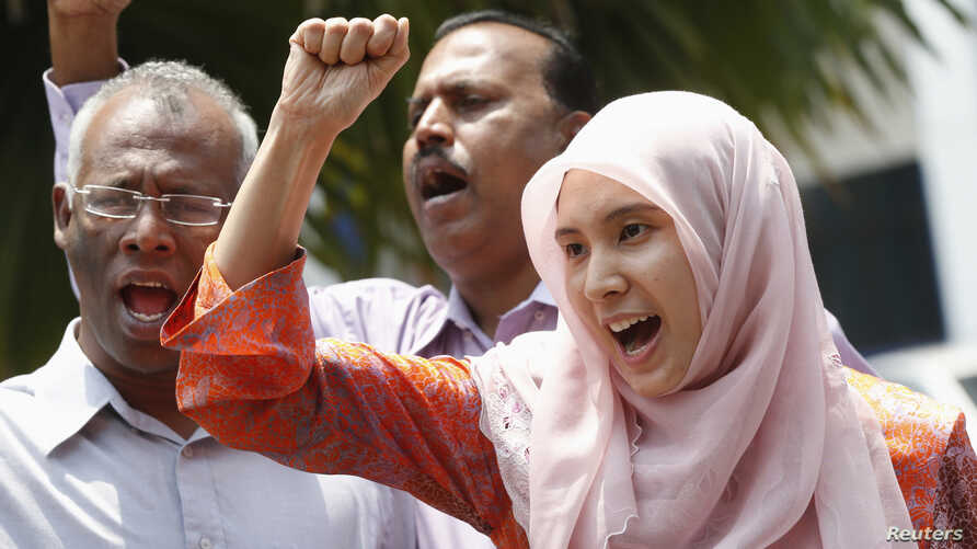 FILE - Nurul Izzah Anwar, right, daughter of imprisoned Malaysian opposition leader Anwar Ibrahim, leads a chant in Kuala Lumpur, March 17, 2015.