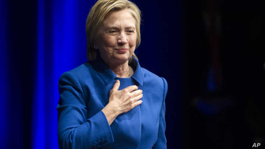 Hillary Clinton places her hand over her hand as she walks to the podium to address the Children's Defense Fund's Beat the Odds celebration at the Newseum in Washington, Nov. 16, 2016.