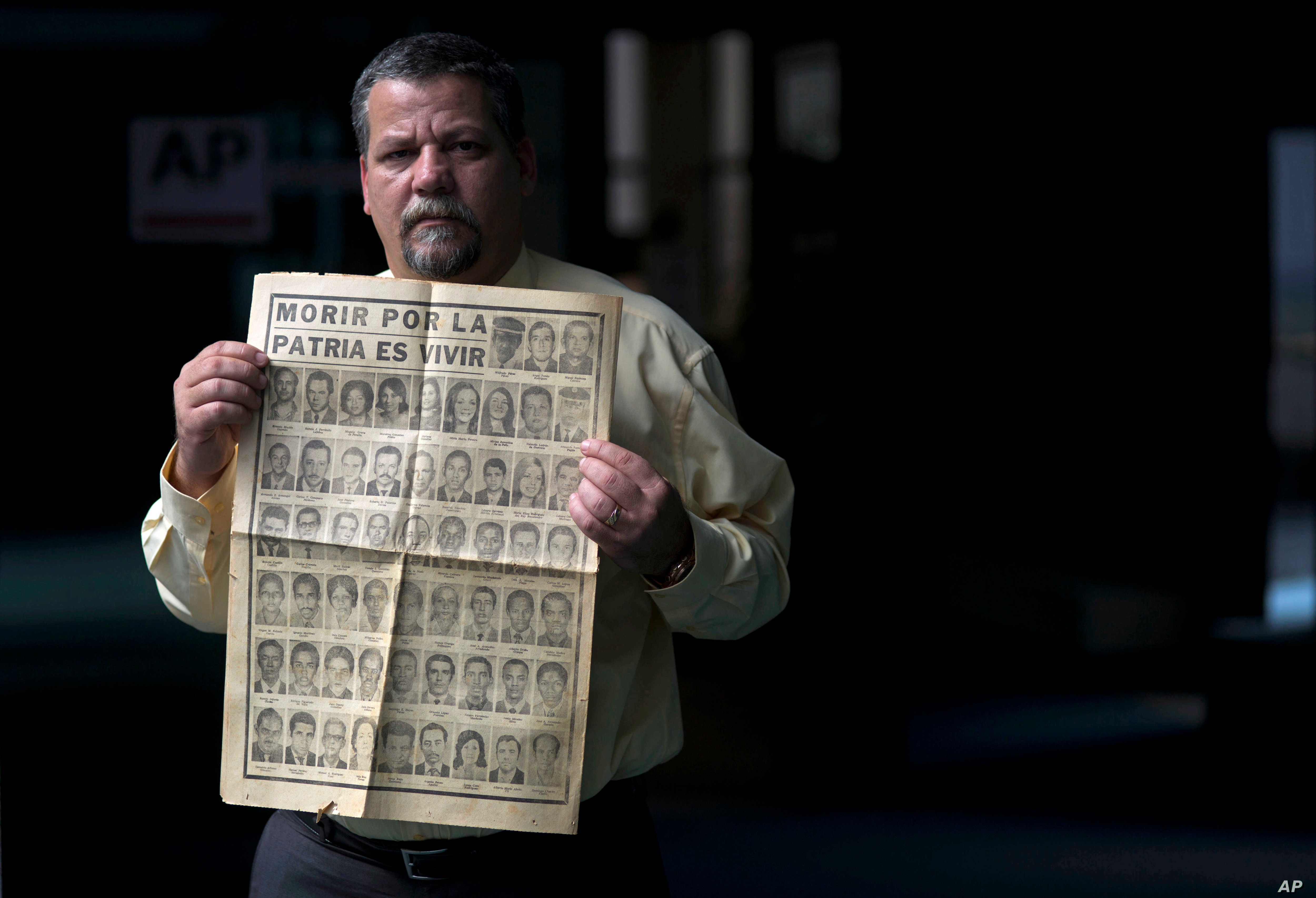 FILE - Camilo Rojo, whose father died in the Cubana Airlines plane that exploded in 1976 while flying from Barbados to Cuba, holds up the Granma newspaper that published the news of the bombing in Havana, Cuba, Feb. 17, 2015.