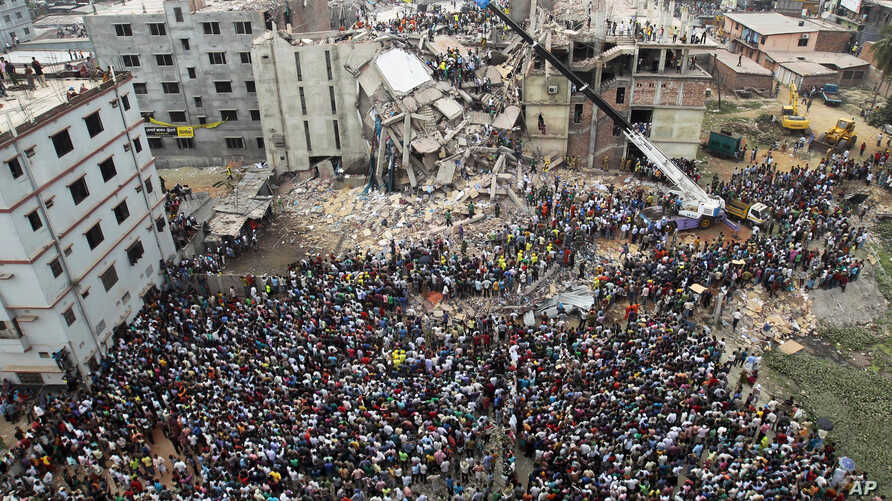 FILE - In this April 25, 2013, photo, people gather as rescuers look for survivors and victims at the site of a building that collapsed a day earlier, in Savar, near Dhaka, Bangladesh.