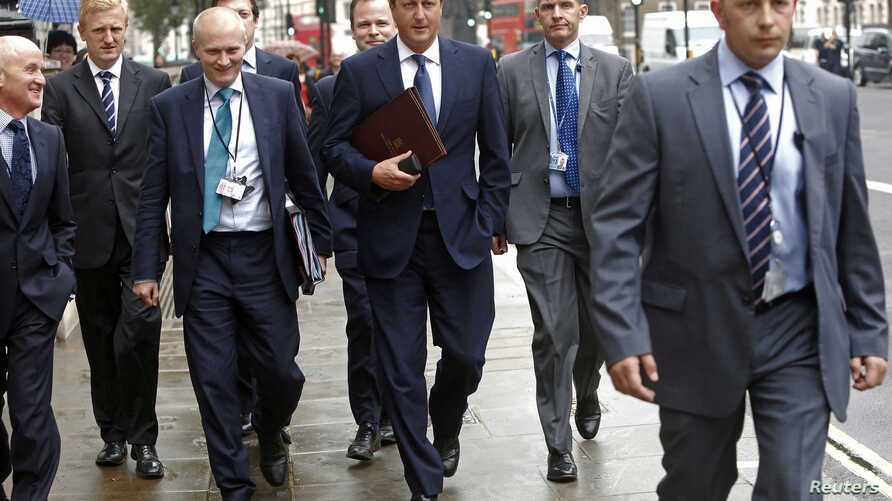 Britain's Prime Minister David Cameron (C) walks to Parliament after leaving Number 10 Downing Street in London Sept. 1, 2014.