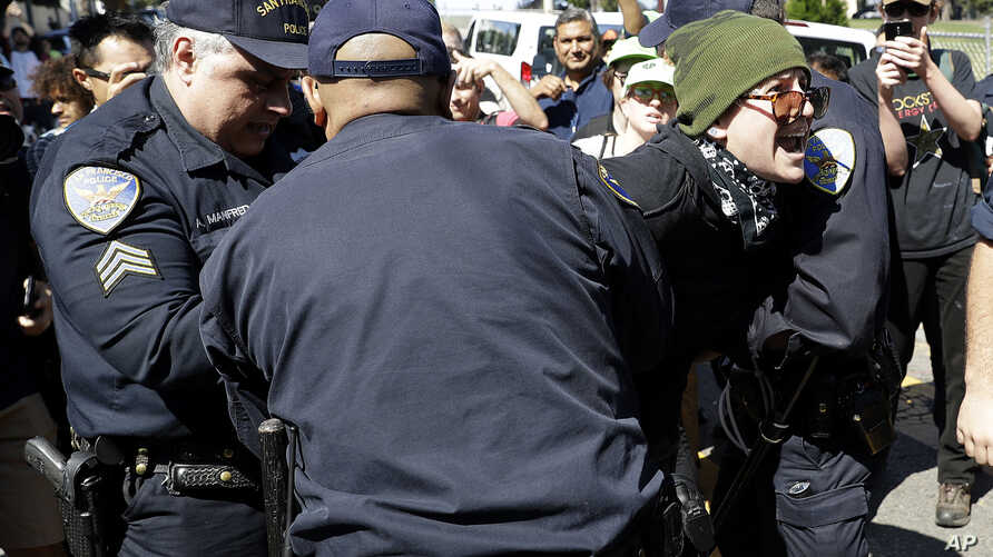 San Francisco Police Officers arrest a protester outside of Alamo Square Park in San Francisco, Aug. 26, 2017.