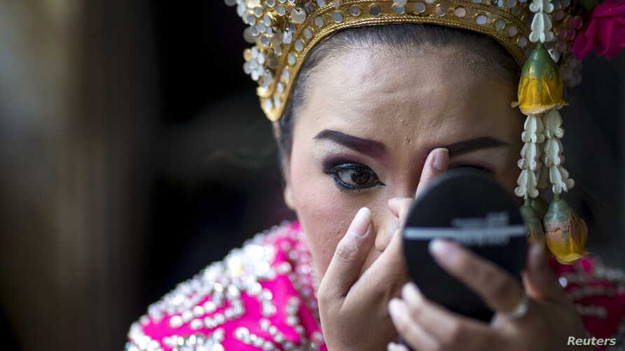 A Thai classical dancer touches up her makeup before performing at the Erawan shrine, site of Monday's deadly blast, in Bangkok, Aug. 21, 2015. Thai tour operators fear the unsolved attack will deter visitors.