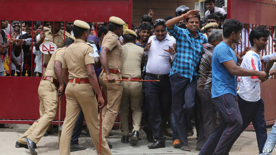 """India Film Kabali: Policemen try to maintain the order of the fans of Indian superstar Rajinikanth as they enter the premises of a cinema hall where the actor's new movie """"Kabali"""" is being screened in Chennai, India, Friday, July 22, 2016."""