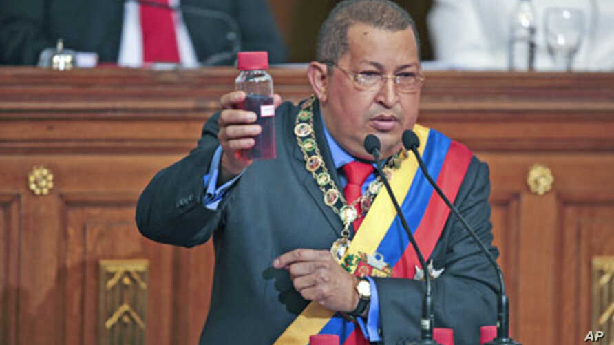 Venezuela's President Hugo Chavez holds a crude oil sample as he deliver his annual state of the nation at the National Assembly in Caracas January 13, 2012.