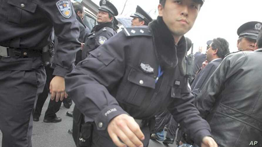 """A policeman tries to stop media from taking photos during the arrest of a man, after calls for a """"Jasmine Revolution"""" protest, organized through the internet, in front of the Peace Cinema in downtown Shanghai, February 27, 2011"""