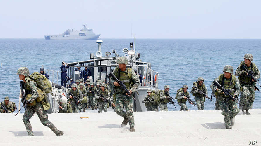 FILE - In this May 9, 2018 photo, Philippine and U.S. Marines storm a beach as part of an amphibious landing exercise during a two-week joint U.S.-Philippines exercise facing the South China Sea in the Philippines.