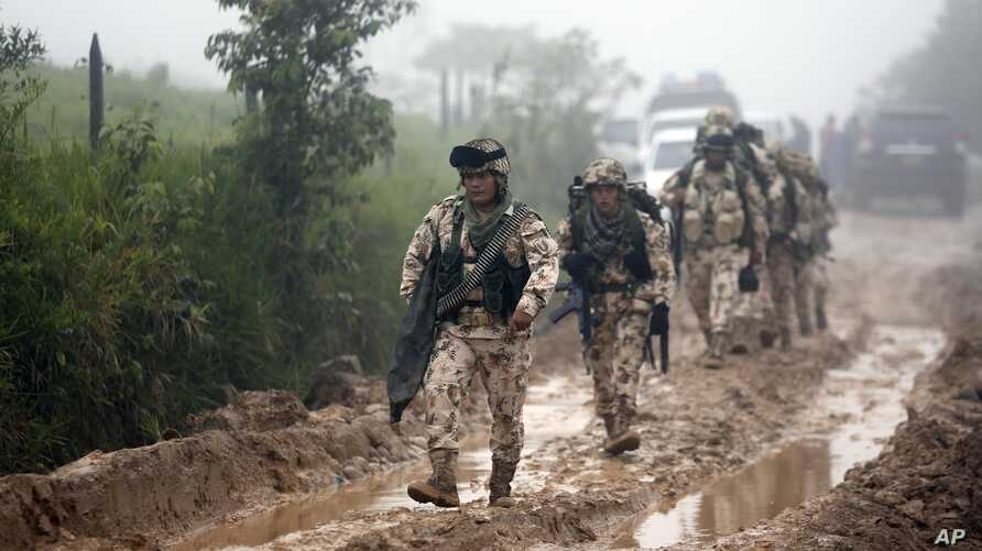 Army soldiers arrive to guard the Mariana Paez demobilization zone, one of many rural camps where FARC rebel fighters are making their transition to civilian life, one day ahead of an event with President Juan Manuel Santos in Buenavista, Colombia, J...