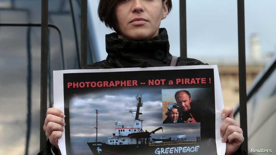 Wife of photojournalist Denis Sinyakov, Alina, protests at headquarters of Russian Investigative Committee, Moscow, Sept. 26, 2013.