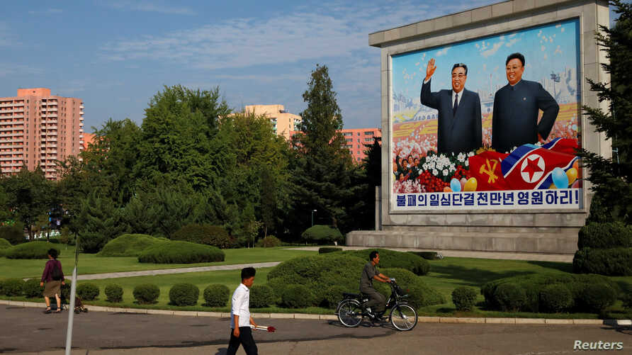 Residents pass a painting of late North Korean leaders Kim Il Sung and Kim Jong Il in Pyongyang, North Korea, Sept. 6, 2018.