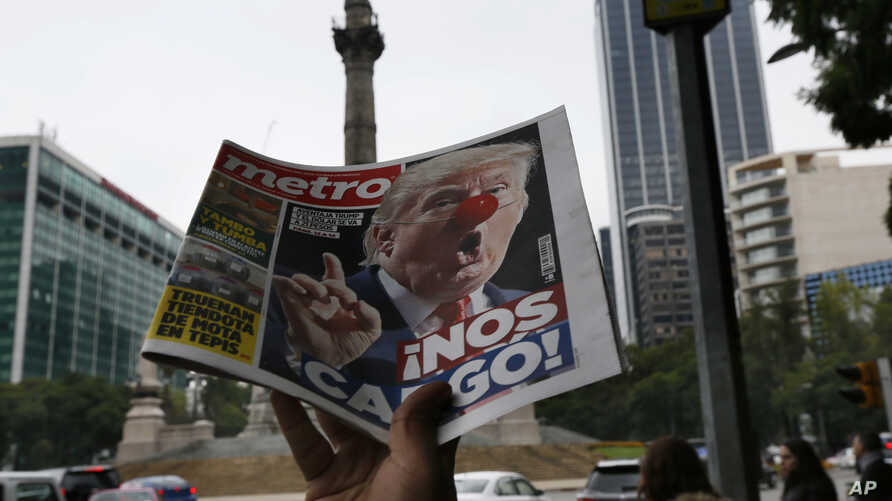 """A street vendor hawks a newspaper emblazoned with an image of Donald Trump with a clown's nose and a headline that reads in Spanish: """"We're screwed!"""" in Mexico City, Nov. 9, 2016."""
