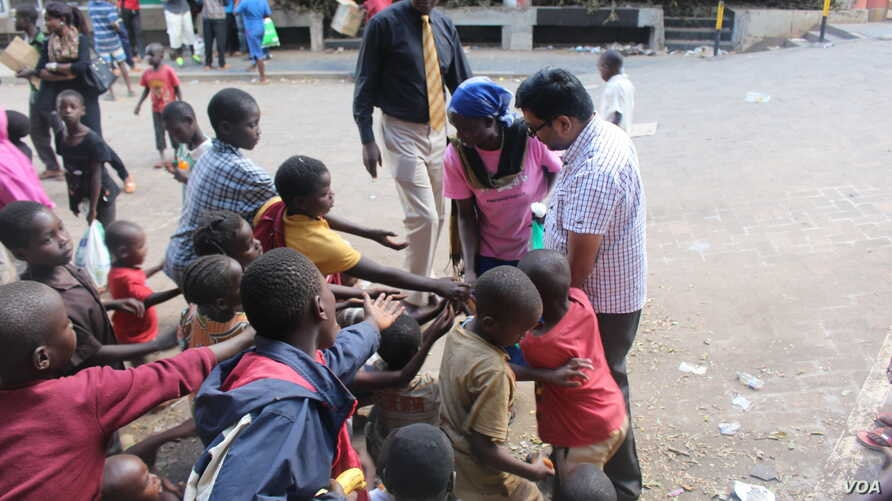 A Homeless of Nairobi volunteer offers children some snacks. Through social media, Clifford Oluoch has been able to collect money from well wishers that has enabled him to run a feeding program and children's home. (VOA/Rael Ombuor)