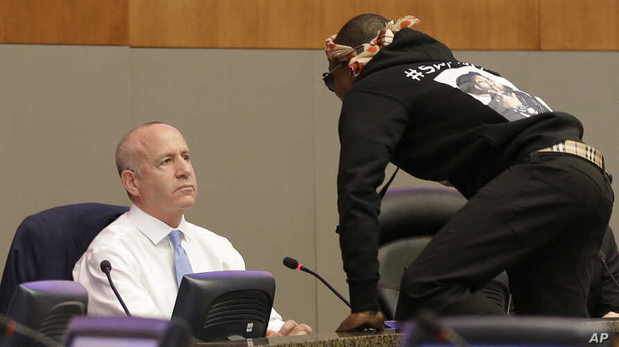 Stevante Clark jumps on the dais and shouts at Sacramento Mayor Darrell Steinberg, left, during a city council meeting in Sacramento, California, March 27, 2018.