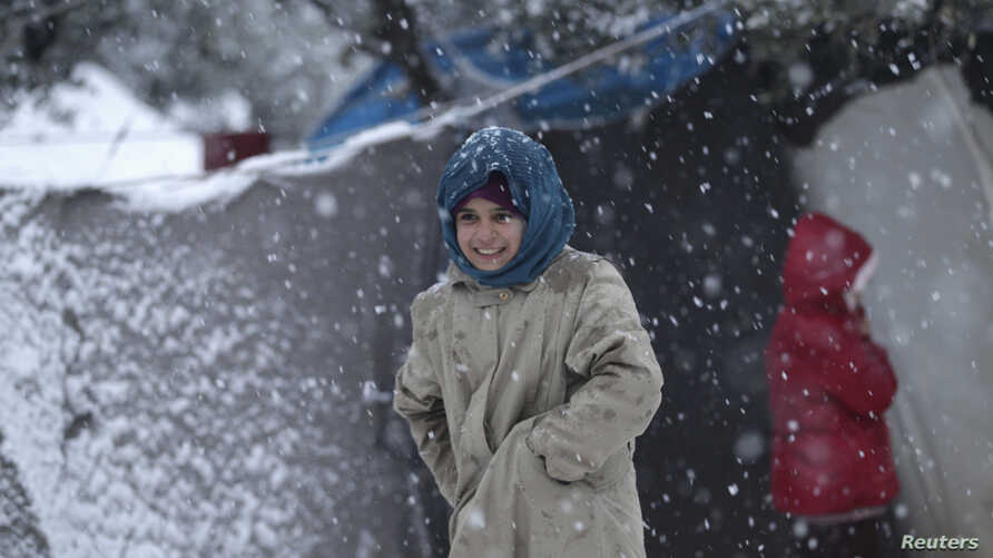An internally displaced child tries to stay warm during a snow storm in northern Idlib, Syria, Jan. 10, 2015.