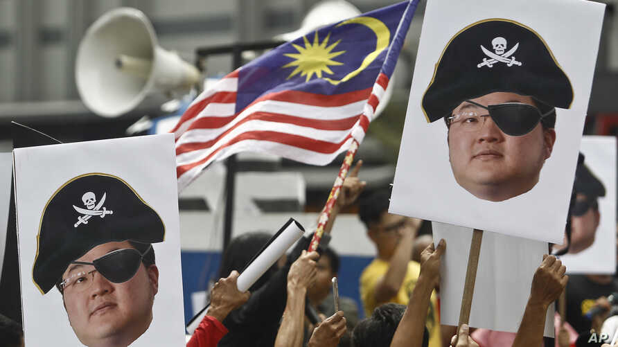 FILE - Protesters hold portraits of Jho Low illustrated as a pirate during a protest in Kuala Lumpur, Malaysia, April 14, 2018.