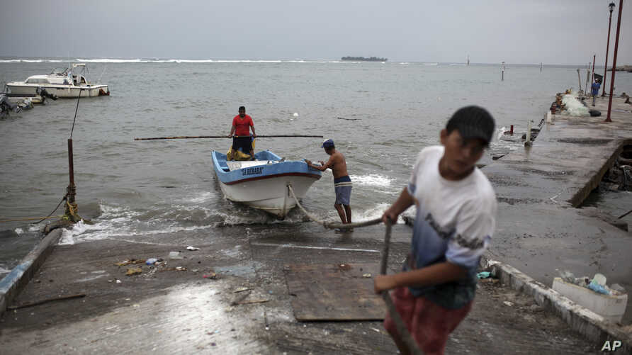 Fishermen drag a boat onto dry land to protect it ahead of the arrival of Tropical Storm Franklin, in the port city of Veracruz, Mexico, Aug. 9, 2017.
