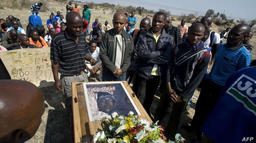 Mineworkers pray over the coffin containing the body of Mpuzeni Ngxande, one of the 34 striking miners that were killed by police on August 16, in front of the rocky outcrop where the men were shot, an informal settlement near the Lonmin mine in Mari...