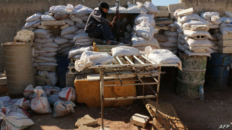 A rebel fighter from the Free Syrian Army (FSA) sits on a barricade as he holds a position on a front line in the northern city of Aleppo on October 1, 2014. US warplanes launched multiple strikes against Islamic State jihadists in both Syria and Ira
