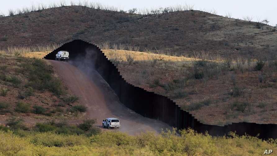 FILE - In this Oct. 2, 2012 file photo, U.S. Border Patrol agents patrol the border fence in Naco, Arizonia.