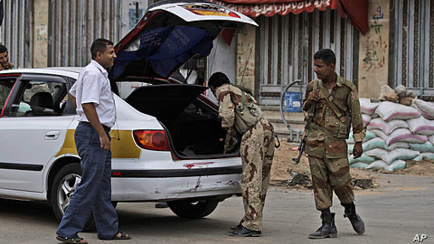 Yemeni army soldiers, check a car, at a checkpoint  in Sana'a, June 11, 2011