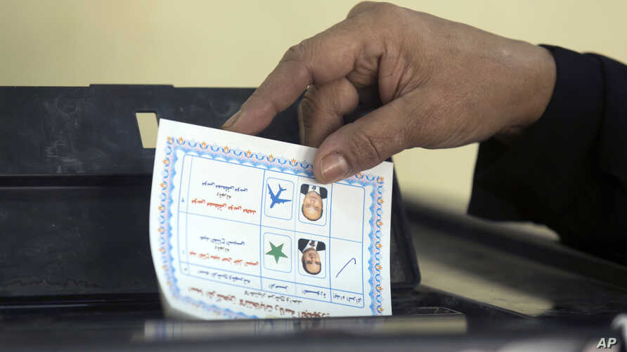 A woman casts her vote during the first day of the presidential election at a polling station in Cairo, Egypt, Monday, March 26, 2018.