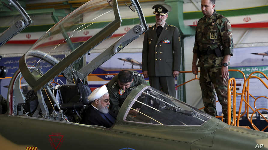 Photo released by official website of the office of the Iranian Presidency shows President Hassan Rouhani being briefed by an air force pilot as he sits in the cockpit of a fighter jet, before an inauguration ceremony of the aircraft, Iran, Aug. 21,