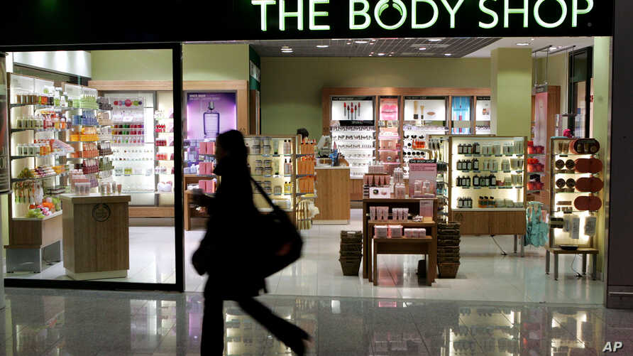 FILE - A woman passes a Body Shop cosmetics store at the airport in Frankfurt, central Germany, March 17, 2006.