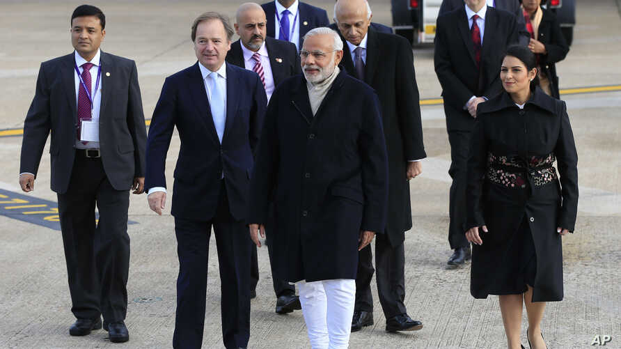 Indian Prime Minister Narendra Modi (c) is greeted by Minister of State for the Foreign and Commonwealth Office, Hugo Swire (l) and MP Priti Patel as he arrives at Heathrow Airport, London, for an official three day visit, Nov. 12,  2015.