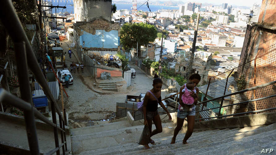 Locals walk in the Morro Da Providencia shantytown in Rio de Janeior, Aug. 17, 2012. Hundreds of families were evicted from Rio favelas because of preparation work needed for the 2014 FIFA World Cup and the 2016 Olympic Games.