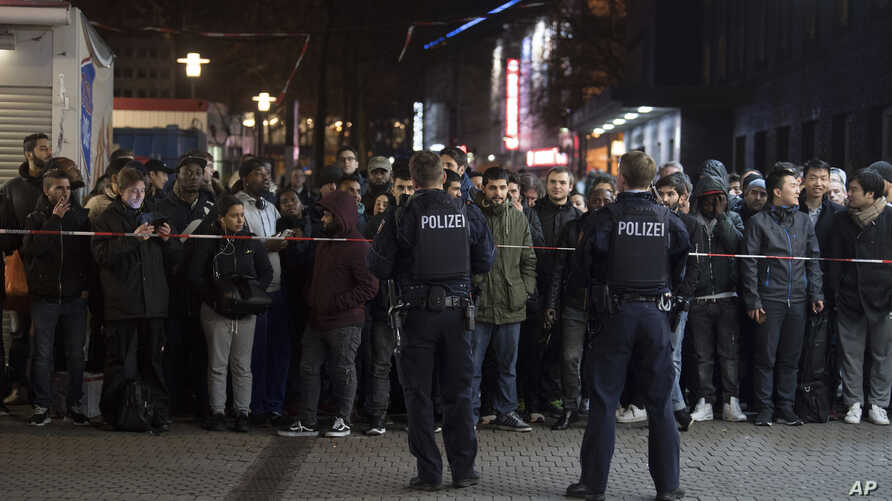 Travelers and bystanders are kept away by police outside the Duesseldorf, western Germany, main station after several people had been injured in an axe attack, March 9, 2017.