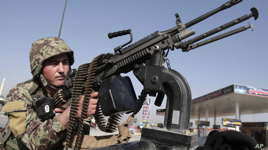 Afghan National army soldier takes on a weapon during a patrol near prayers gather for Eid al-Adha near a mosque in the outskirt of Jalalabad east of Kabul, Afghanistan, Oct. 26, 2012.