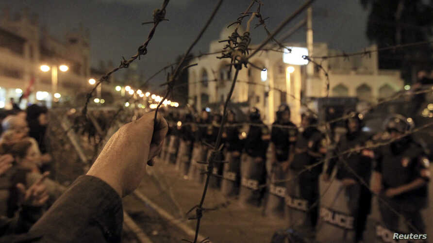 Egyptian protesters stand in front of barbed wire beyond the presidential palace in Cairo, December 4, 2012.