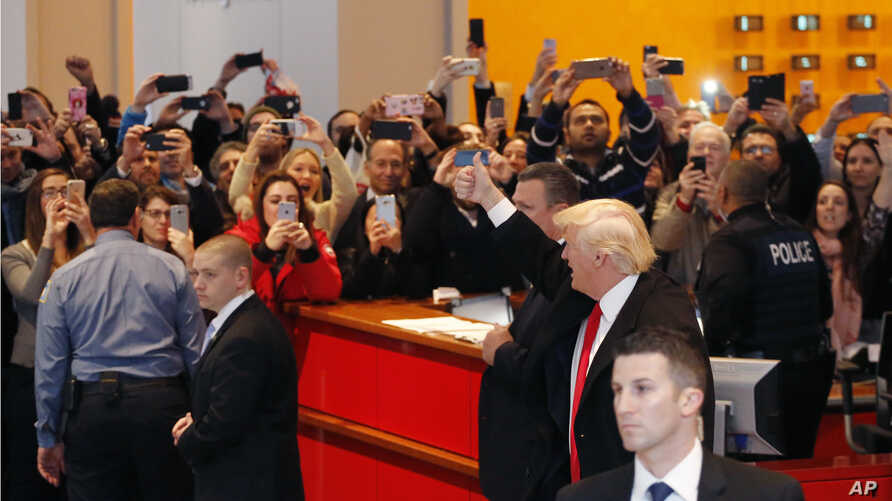 President-elect Donald Trump gives a thumbs-up to the crowd as he leaves the New York Times building following a meeting, Nov. 22, 2016, in New York.